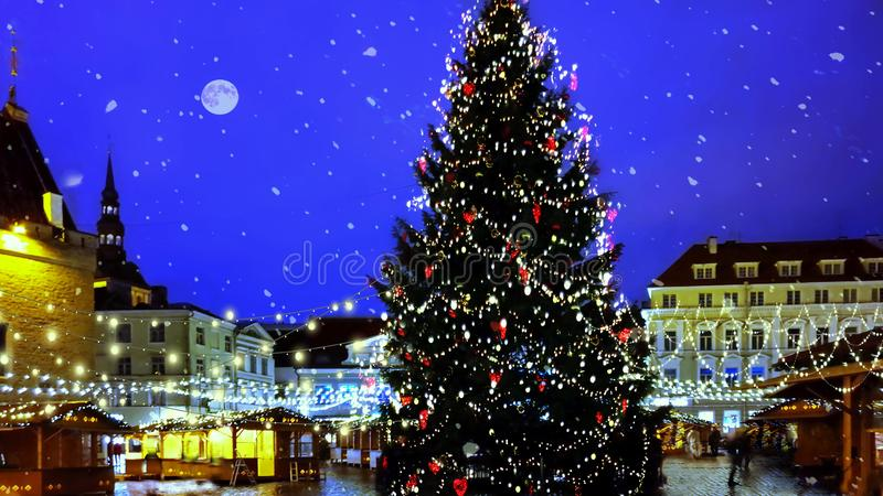 Christmas tree holiday in Tallinn old town square night city blurring light and snowflakes fall stock images