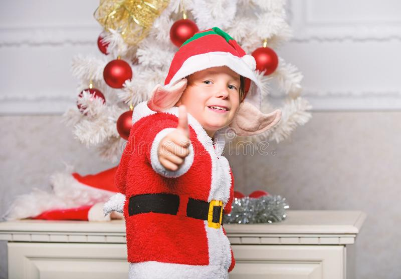 Christmas tree ideas for kids. Boy kid dressed as cute elf magical creature white artificial ears and red hat near. Christmas tree. Christmas elf costume for royalty free stock photo