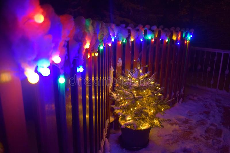 Christmas tree with christmas lights and snow on a balcony stock photo