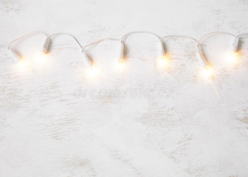 Christmas tree lights on white shabby background. Minimal. Copy space royalty free stock photography