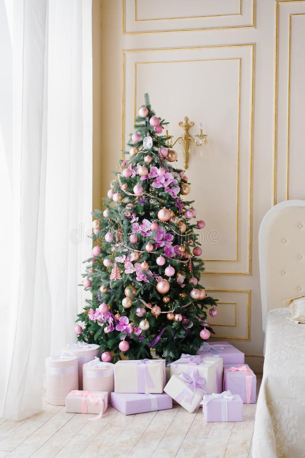 Christmas tree with lilac pink toys and gifts under the Christmas tree in beige stylish classic living room stock photos