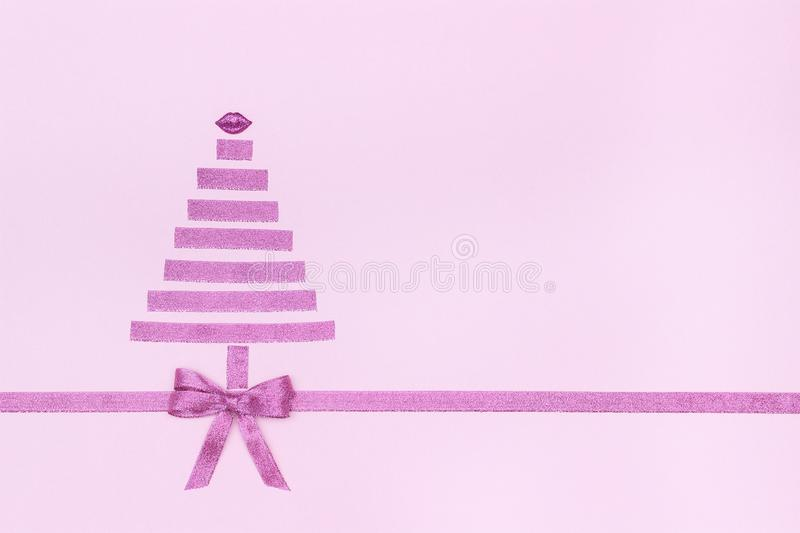 Christmas tree and lips from decorative shiny ribbon with bow on pastel pink stock image