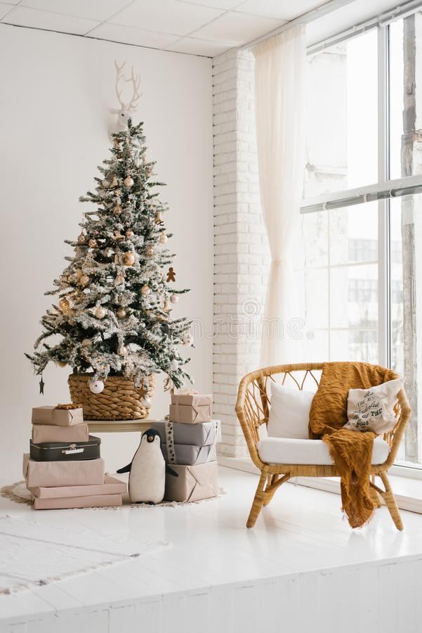 Christmas tree in the living room in bright colors, a chair from the rotunda. Near the floor-to-ceiling window royalty free stock images