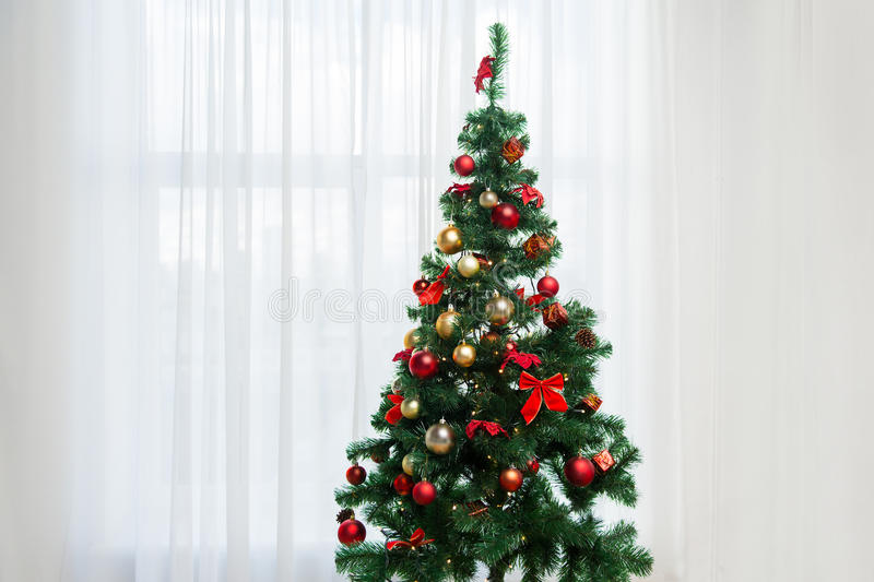 Christmas tree in living room over window curtain. Holidays, celebration and home concept - christmas tree in living room over window curtain stock images