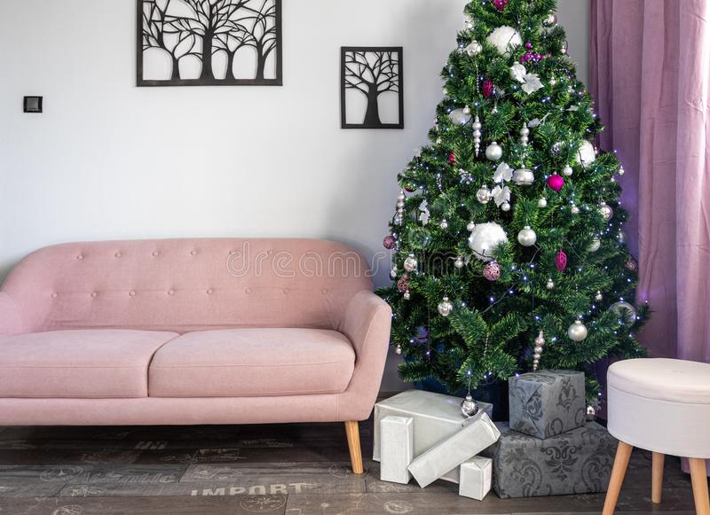 Christmas tree in living room, silver Christmas gifts, pink sofa 2.  royalty free stock images
