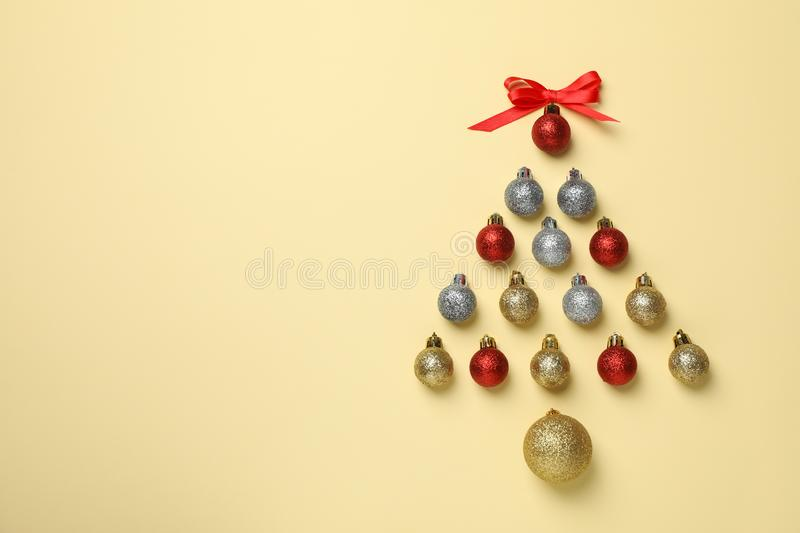 Christmas tree made of baubles on beige background. Space for text royalty free stock photo