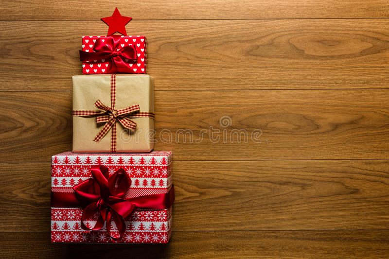 Christmas tree made of beautifully wrapped presents on wooden background stock images