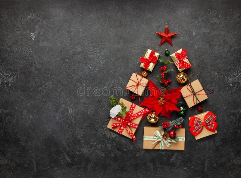 Christmas tree made from Christmas gifts and decorations on black background. Creative winter holiday concept. Flat lay royalty free stock photography