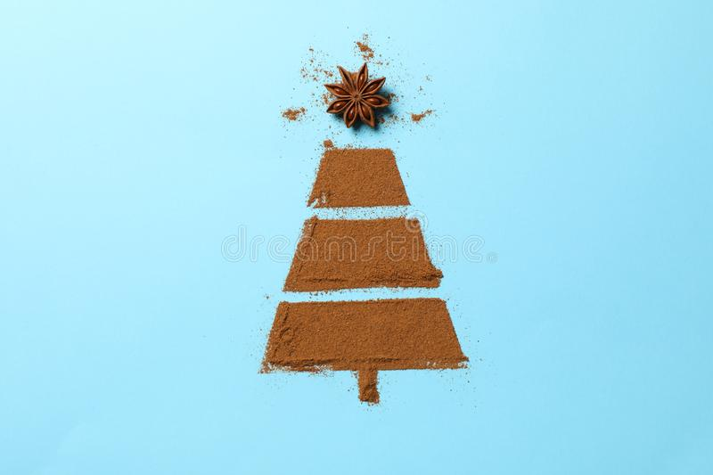 Christmas tree made of cinnamon powder on blue background royalty free stock photography