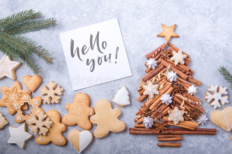 Christmas tree made of cinnamon with traditional gingerbread cookies on grey background, space for text. X-mas or New year festive royalty free stock image