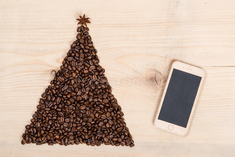 Christmas tree made from coffee beans and phone on wooden background. Top view, copy space.Winter holidays concept. Christmas tree made from coffee beans and royalty free stock images