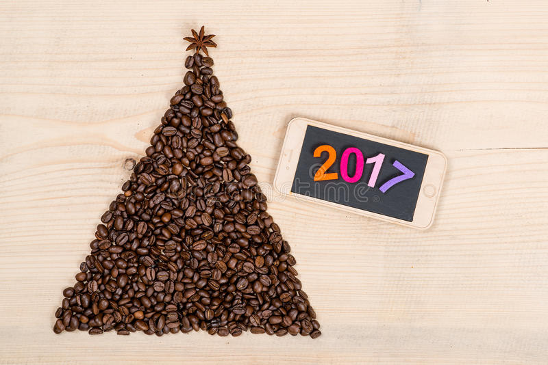 Christmas tree made from coffee beans and phone on wooden background. Top view.Winter holidays concept. Christmas tree made from coffee beans and phone on a stock photography