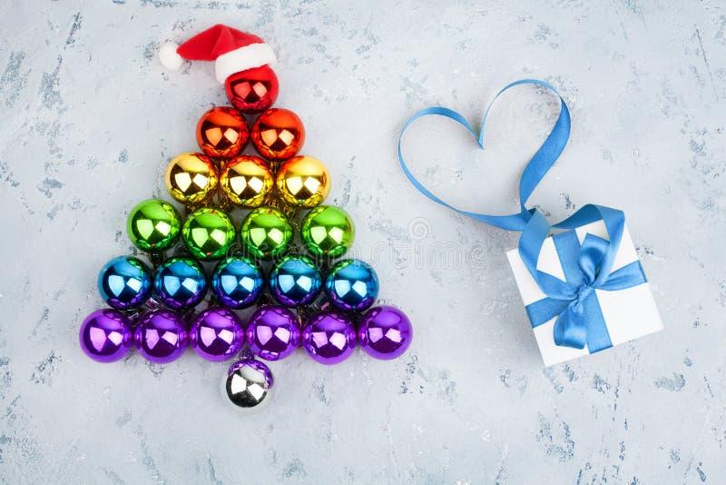 Christmas tree made of decorations balls LGBT community rainbow flag colors, Santa Claus hat, gift box, blue ribbon shape of heart stock photography