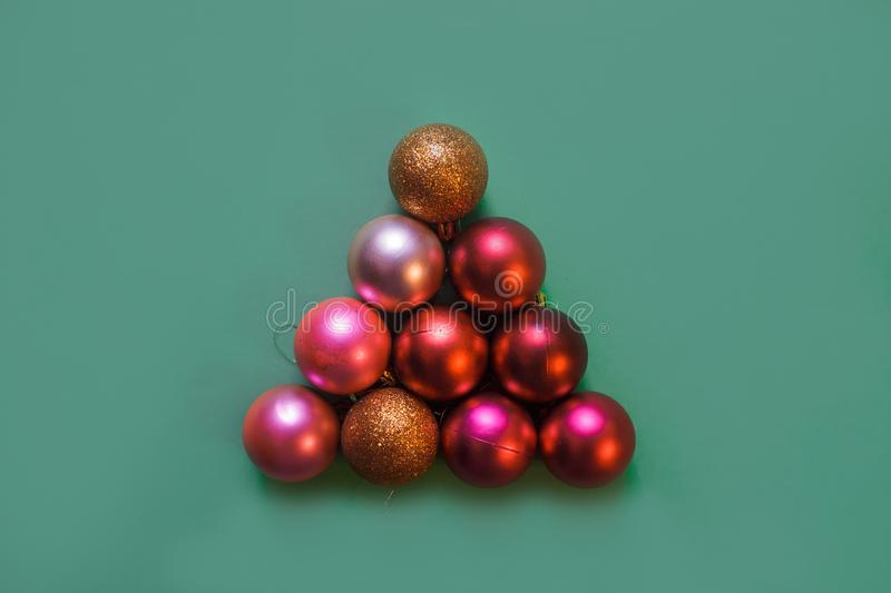 Christmas tree made by gold, red and pink Christmas balls on the green background, copy space. Christmas tree made by gold, red and pink Christmas balls on the royalty free stock photography