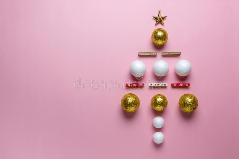 Christmas tree made of gold, white and red glitter ball decoration on pink background. New Year minimal concept. Flat lay royalty free stock images