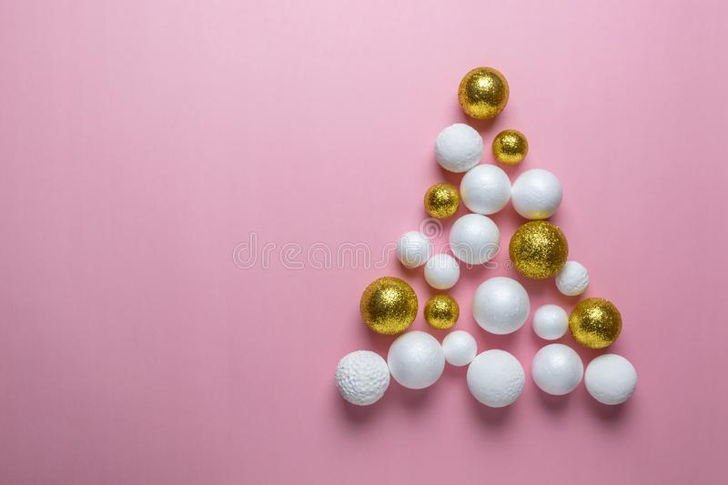 Christmas tree made of gold, white and red glitter ball decoration on pink background. New Year minimal concept. Flat lay royalty free stock image