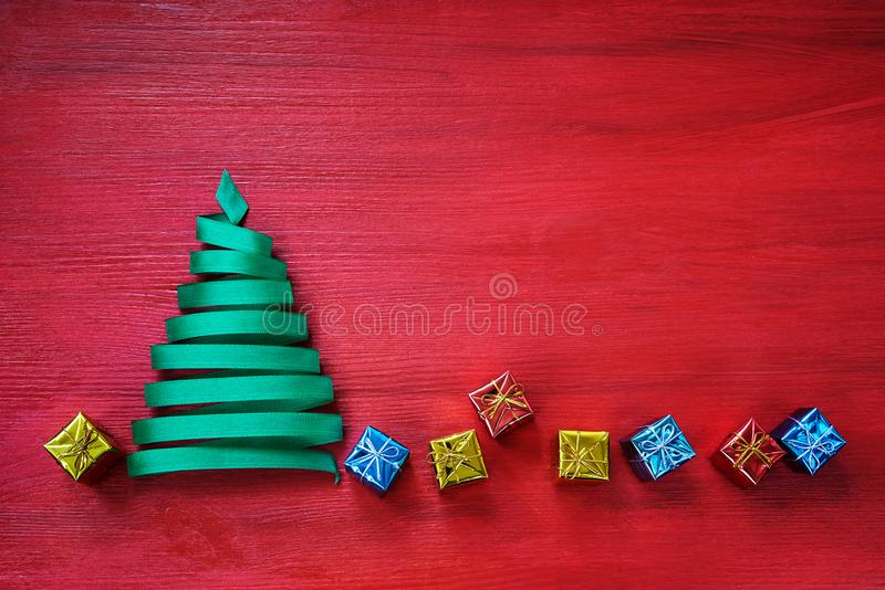 Christmas tree made from green ribbon with small gifts on red background. royalty free stock photos