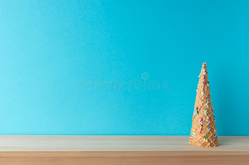 Christmas tree made of ice cream cone with sweet color decoration on blue background. Christmas or New Year minimal concept.  stock image