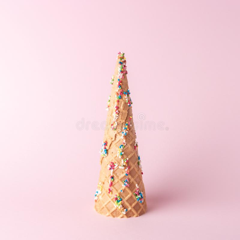 Christmas tree made of ice cream cone with sweet color decoration on pink background. Christmas or New Year minimal concept.  royalty free stock photos