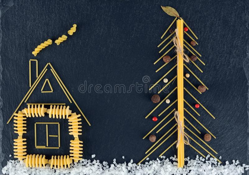 Christmas tree made with italian spaghetti with salt, pepper, on a slate background. New Year background made with pasta royalty free stock photo