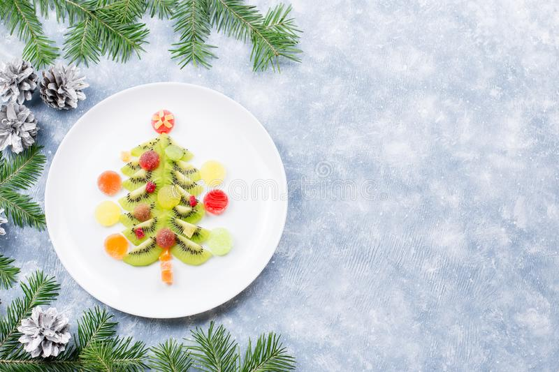 Christmas tree made of kiwi and fruit jelly on a plate with fir branches and decorations. Top view, copy space royalty free stock photos