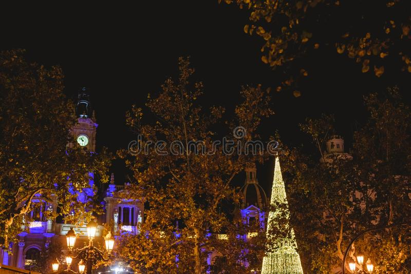 Christmas tree made with luminous LEDs at night next to the historical building of the city hall of Valencia, Spain. stock image