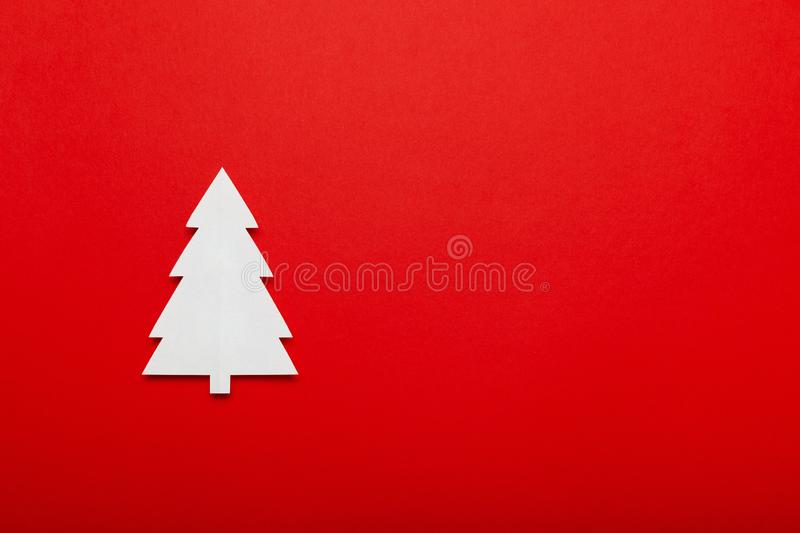 Christmas tree made of paper on a red background. Merry Christmas advertising for covers, invitations, posters, banners, flyers,. Placards royalty free stock image