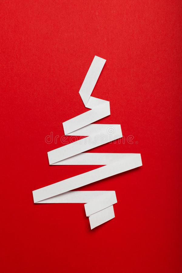 Christmas tree made of paper on a red background. Merry Christmas advertising for covers, invitations, posters, banners, flyers,. Placards royalty free stock photos