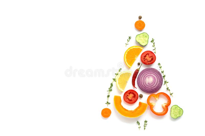 Christmas tree made of pieces of vegetables and fruits on a white background. The concept of vegan and vegetarian food. Top view,. Flat lay, copy space royalty free stock images