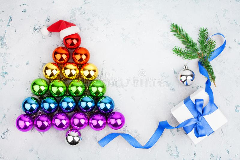 Christmas tree made of shiny decorations balls LGBT community rainbow flag colors, Santa Claus hat, gift box, blue ribbon, pine stock photography
