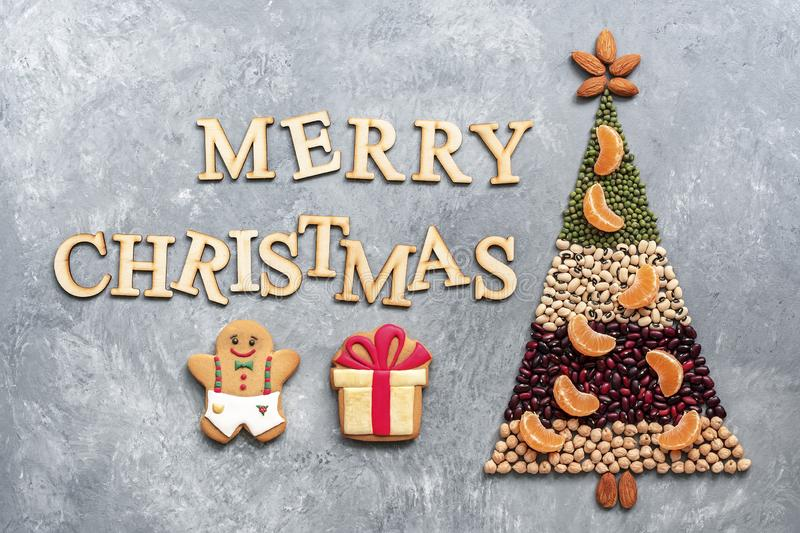Christmas tree made of various legumes decorated with slices of tangerines and gingerbread man and a gift on a gray rustic stock photos
