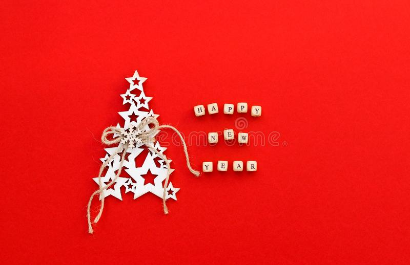 Christmas tree made of white wooden stars with snowflake and craft rope and words Happy New Year written on small bricks on bright. Red background. Minimalism stock photo