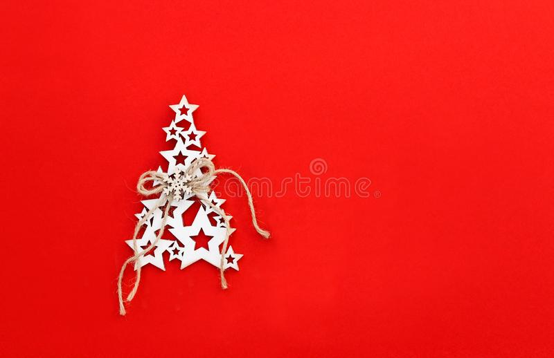 Christmas tree made of white wooden stars with snowflake and craft twine on bright red background with copy space. stock image