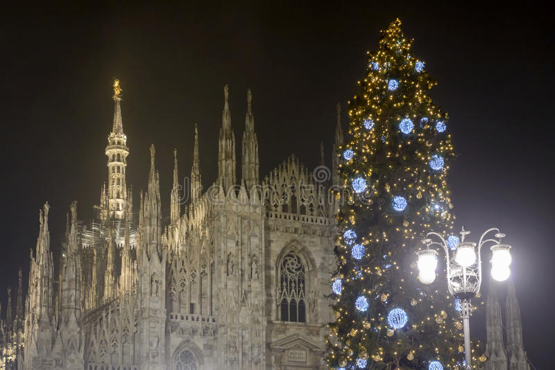 Christmas Tree and Madunina, Milan. In Xmas time view of Christmas tree in front of staples of Minster and its gilt statue. Shot in foggy winter light in Milan royalty free stock photos