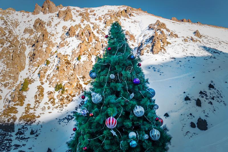 Christmas tree in mountain snow forest. Christmas tree decorated with large balls on the background of the mountains royalty free stock photo