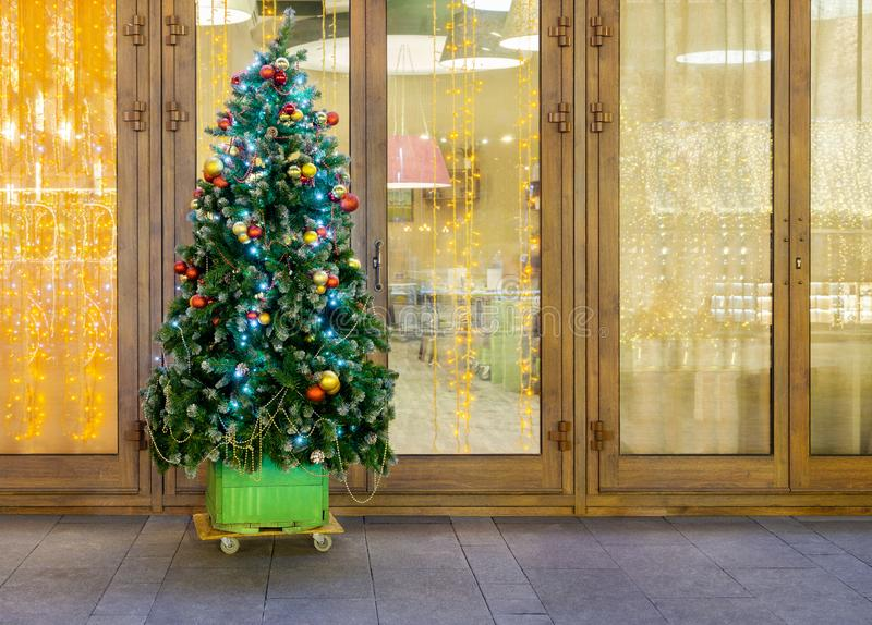 Christmas tree near cafe. Christmas tree with New Year decorations is near cafe windows. Evening time royalty free stock photo