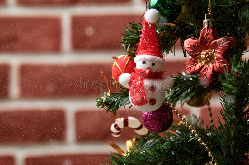 Christmas tree with ornament decorating items such as  colorful ball, red flower and snowman with snow fall stock images