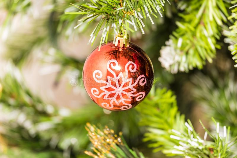 The christmas tree ornament toy, red ball or sphere with white snowflake on the fluffy artificial pine or fur branch. With red and blue garland stock images