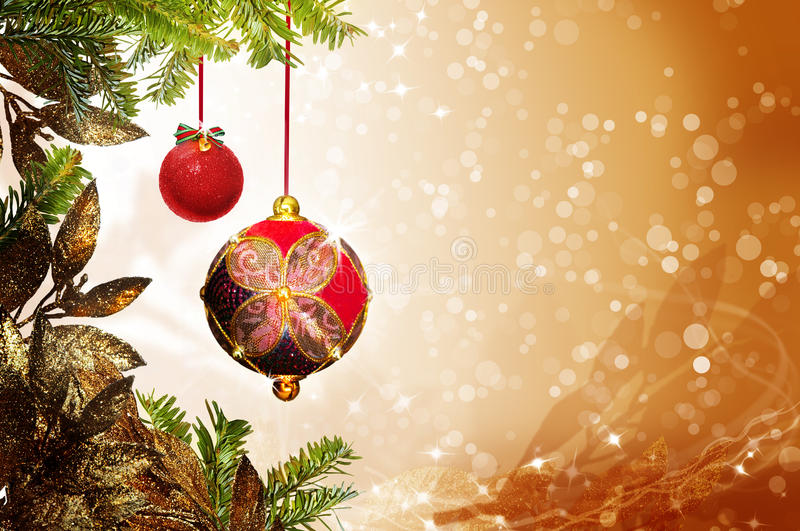 Christmas tree ornaments. Two Christmas tree ornaments hanging from pine branches with a golden background
