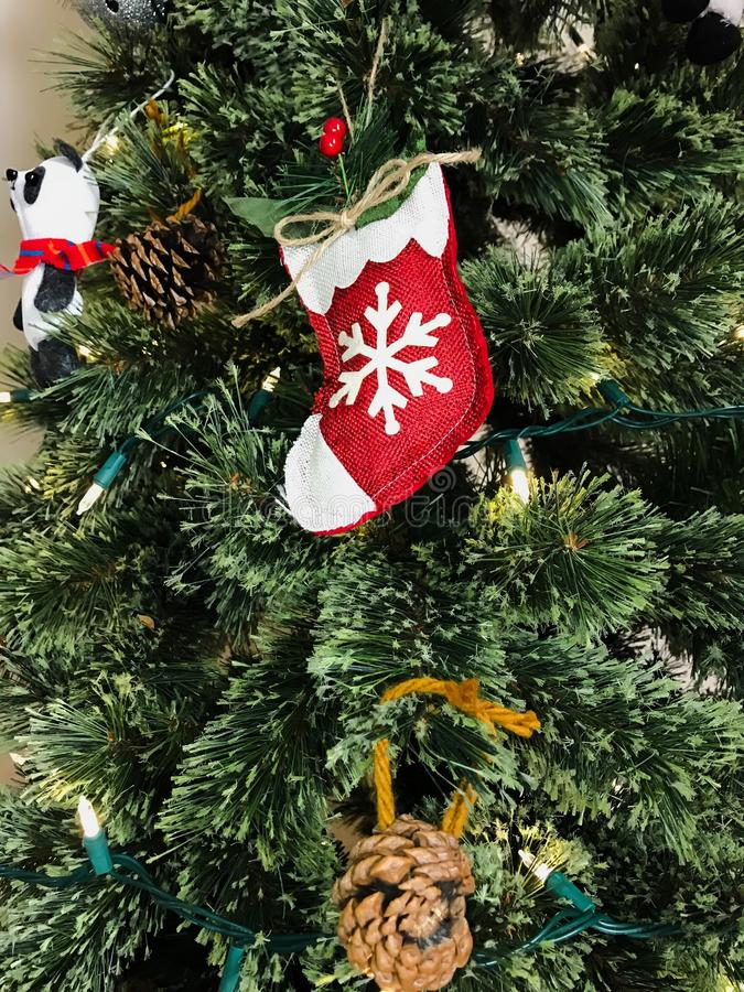 Christmas tree ornaments. Red small stocking hanging on Christmas tree royalty free stock images