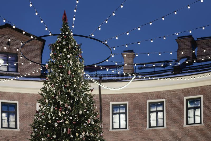 Christmas tree outside outside in the lights and garlands next to the old brick house. Festive background stock image