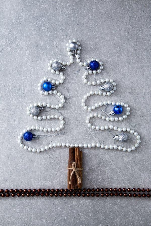 Christmas tree of pearls, cinnamon sticks and Christmas balls. T stock photo