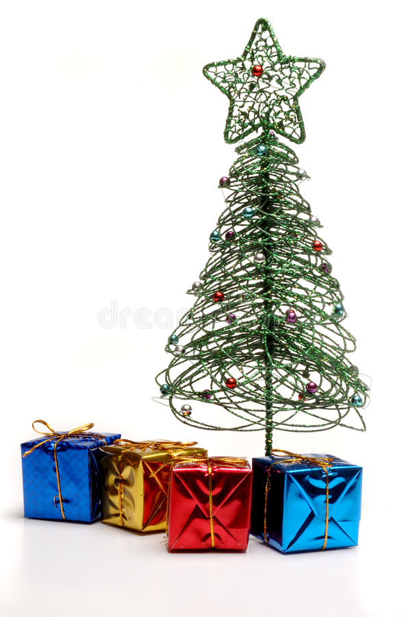Christmas tree and presents. A beautiful modern artificial christmas tree with big star on top standing behind colorful wrapped presents in blue, gold, red and stock photo