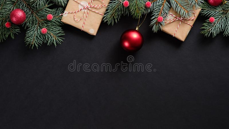 Christmas tree with red decorations and gifts on black background. Flat lay, top view, overhead. Christmas banner mockup royalty free stock images