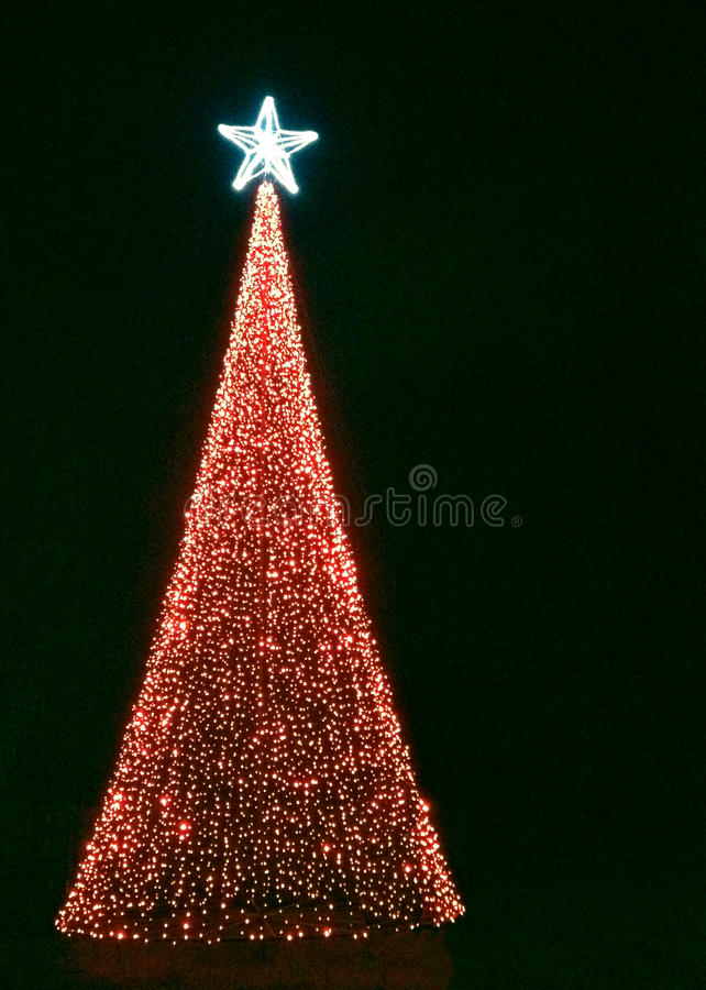 Christmas tree with red lights and bright star. Christmas tree made from lights against black night background royalty free stock images