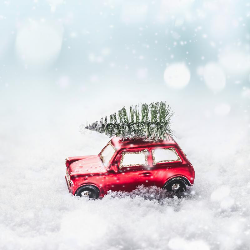 Christmas tree on red toy retro car in snow, through snowy winter wonder land with snowfall and bokeh. royalty free stock images