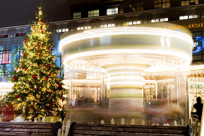 Christmas tree and a rotating carousel. Bright illumination. Fair in Moscow. Christmas Fair. Christmas tree and a rotating carousel. Bright illumination. Fair stock photography