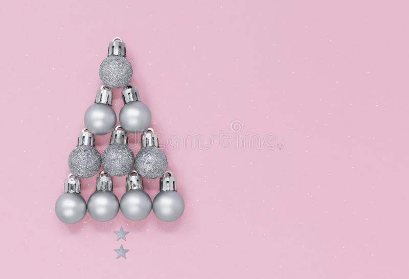 Christmas tree shape made of silver baubles and stars isolated on a pastel pink speckled background, with copy space stock photography