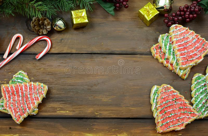 Christmas tree shaped sugar cookies, candy canes pine branches with cones, mini gifts and jingle bells on a wide-plank rustic wood royalty free stock photo