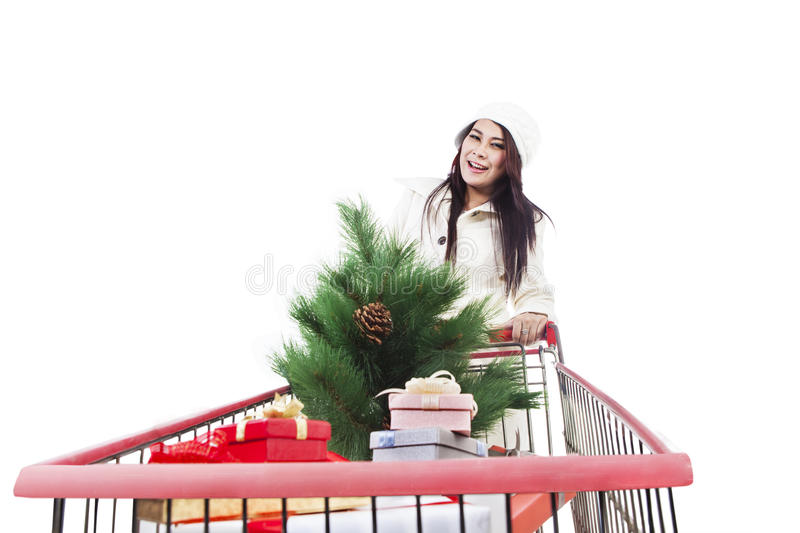 Christmas tree shopping isolated in white. Woman is shopping for Christmas tree and boxes inside a trolley, isolated in white royalty free stock images